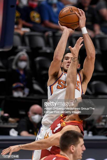 Devin Booker of the Phoenix Suns shoots over Facundo Campazzo of the Denver Nuggets during the first quarter at Ball Arena on Sunday, June 13, 2021....