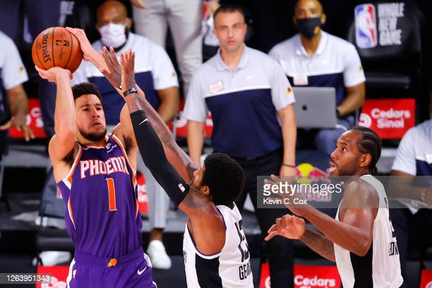 Devin Booker of the Phoenix Suns shoots the game winning basket over Paul George of the LA Clippers at The Arena at ESPN Wide World Of Sports Complex...
