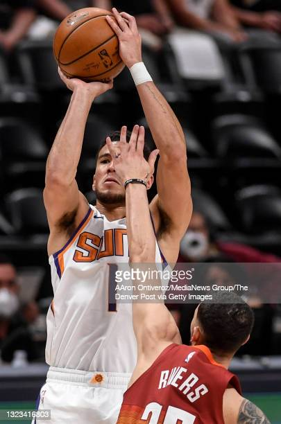 Devin Booker of the Phoenix Suns shoots with a hand in his face from Austin Rivers of the Denver Nuggets during the second quarter at Ball Arena on...