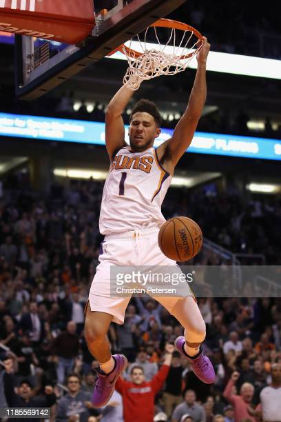 Devin Booker of the Phoenix Suns slam dunks the ball against the Philadelphia 76ers during the second half of the NBA game at Talking Stick Resort...