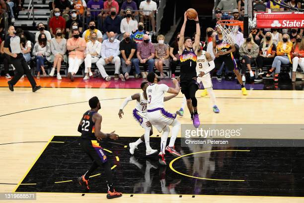 Devin Booker of the Phoenix Suns slam dunks the ball past Anthony Davis of the Los Angeles Lakers during the first half of Game One of the Western...