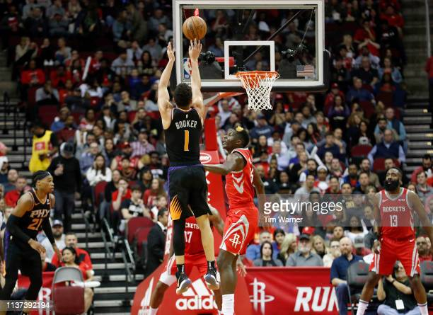 Devin Booker of the Phoenix Suns takes a three point shot defended by Clint Capela of the Houston Rockets in the first half at Toyota Center on March...