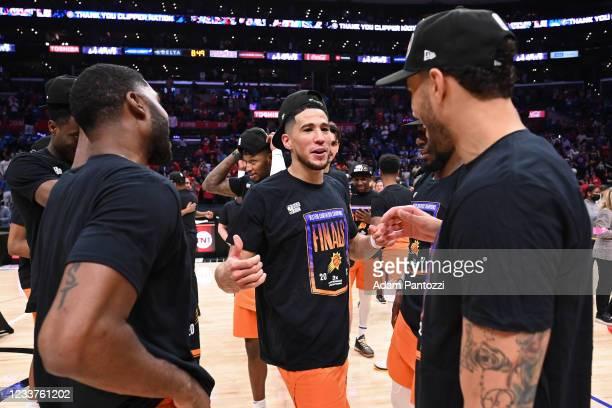 Devin Booker of the Phoenix Suns talks to E'Twaun Moore of the Phoenix Suns and Abdel Nader of the Phoenix Suns after the game against the LA...