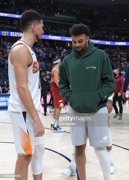 Devin Booker of the Phoenix Suns talks with Jamal Murray of the Denver Nuggets during Round 2, Game 4 of the 2021 NBA Playoffs on June 13, 2021 at...