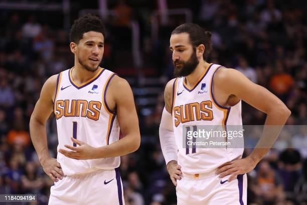 Devin Booker of the Phoenix Suns talks with Ricky Rubio during the second half of the NBA game against the Utah Jazz at Talking Stick Resort Arena on...