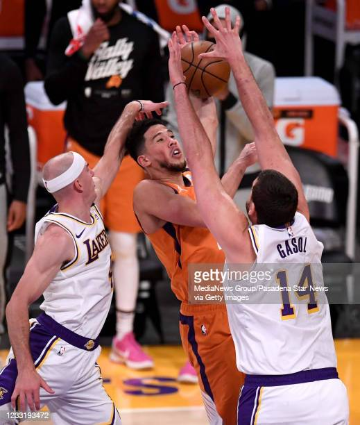 Devin Booker of the Phoenix Suns turns the ball over against Alex Caruso and teammate Marc Gasol of the Los Angeles Lakers in the fourth quarter of...