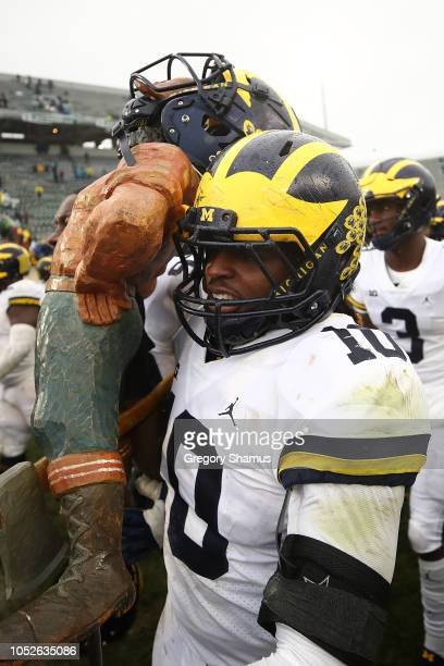 Devin Bush of the Michigan Wolverines carries the Paul Bunyan trophy off the field after beating the Michigan State Spartans 217 at Spartan Stadium...