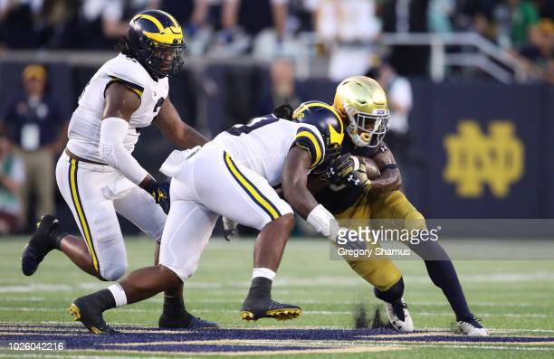 Devin Bush of the Michigan Wolverines tackles Jafar Armstrong of the Notre Dame Fighting Irish in the first quarter at Notre Dame Stadium on...
