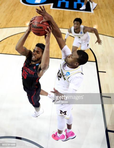 Devin Davis of the Houston Cougars drives past MuhammadAli AbdurRahkman of the Michigan Wolverines during the second round of the 2018 NCAA Men's...