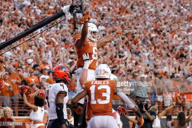 Devin Duvernay of the Texas Longhorns celebrates with teammates after a touchdown reception in the second quarter against the Oklahoma State Cowboys...