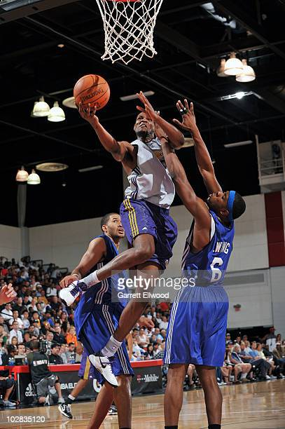 Devin Ebanks of the Los Angeles Lakers goes to the basket against Patrick Ewing Jr #6 of the New York Knicks during the NBA Summer League on July 12...