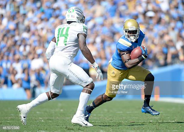 Devin Fuller of the UCLA Bruins turns upfield after his catch in front of Ifo EkpreOlomu of the Oregon Ducks during the second quarter at Rose Bowl...