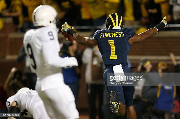 Devin Funchess of the Michigan Wolverines celebrates a first quarter touchdown behind Jordan Lucas of the Penn State Nittany Lions on October 11 2014...