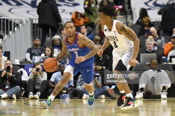 Devin Gage of the DePaul Blue Demons dribbles up court past James Akinjo of the Georgetown Hoyas during a college basketball game at the Capital One...