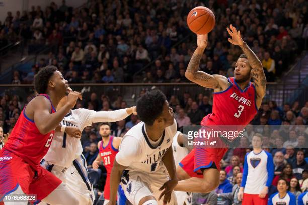 Devin Gage of the DePaul Blue Demons passes the ball to Femi Olujobi against Jahvon Quinerly and Saddiq Bey of the Villanova Wildcats in the second...