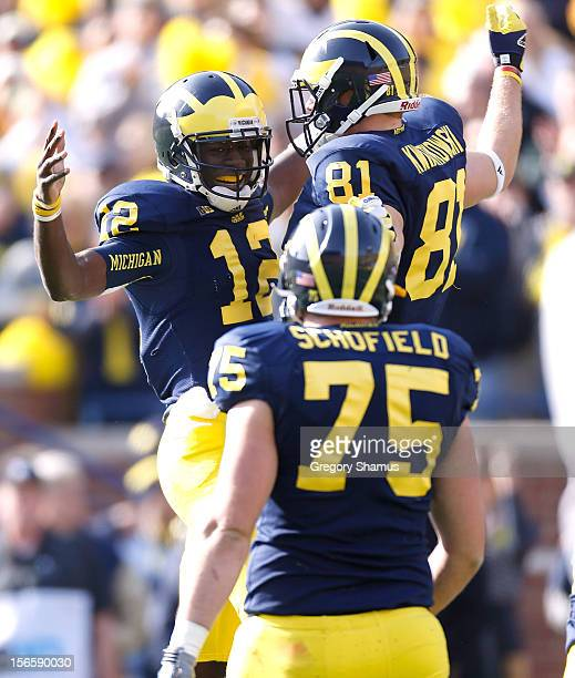 Devin Gardner of the Michigan Wolverines celebrates a first quarter touchdown with Mike Kwiatkowski and Michael Schofield of the Michigan Wolverines...
