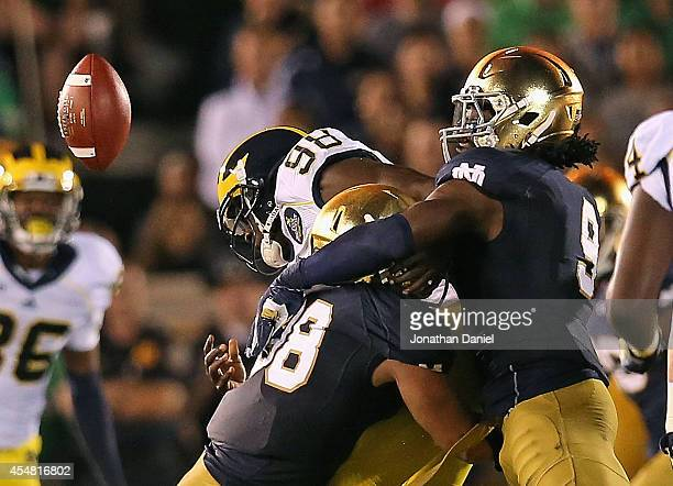 Devin Gardner of the Michigan Wolverines fumbles the ball as he is hit by Joe Schmidt abd Jaylon Smith of the Notre Dame Fighting Irish at Notre Dame...