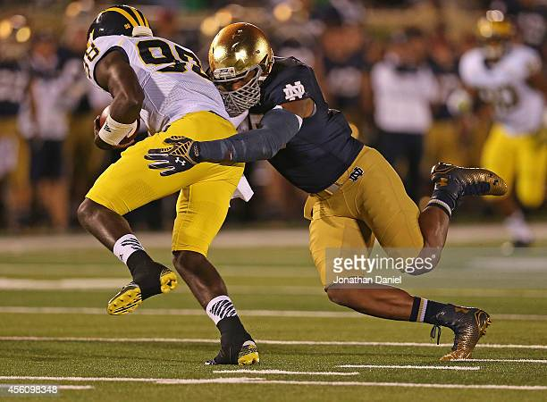 Devin Gardner of the Michigan Wolverines is sacked by Romeo Okwara of the Notre Dame Fighting Irish at Notre Dame Stadium on September 6, 2014 in...