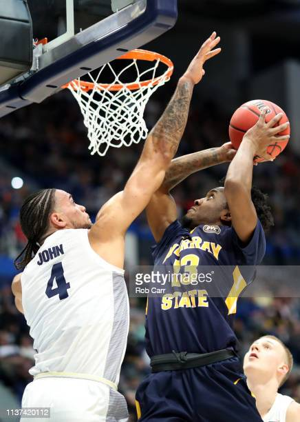 Devin Gilmore of the Murray State Racers looks for the basket over Theo John of the Marquette Golden Eagles during their first round game of the 2019...