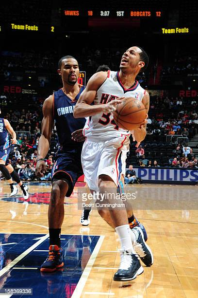 Devin Harris of the Atlanta Hawks drives to the basket against Ramon Sessions of the Charlotte Bobcats at Philips Arena on December 13 2012 in...