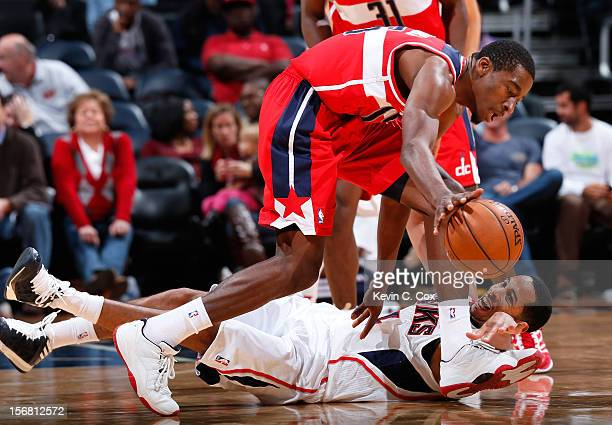 Devin Harris of the Atlanta Hawks reaches for a steal against Jordan Crawford of the Washington Wizards at Philips Arena on November 21 2012 in...