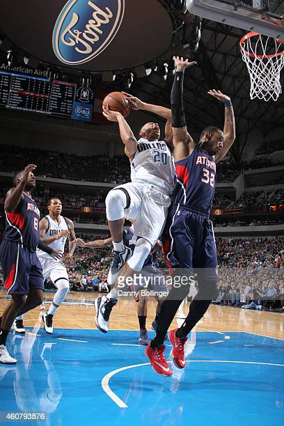 Devin Harris of the Dallas Mavericks goes in for the layup against Mike Scott of the Atlanta Hawks on December 22 2014 at the American Airlines...