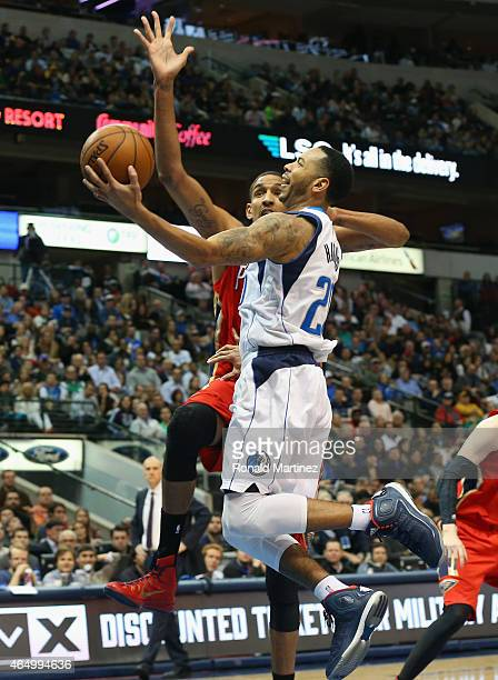Devin Harris of the Dallas Mavericks takes a shot against Alexis Ajinca of the New Orleans Pelicans at American Airlines Center on March 2, 2015 in...
