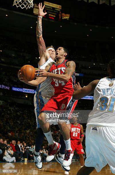 Devin Harris of the New Jersey Nets goes to the basket against Chris Andersen and Nene of the Denver Nuggets on November 24 2009 at the Pepsi Center...