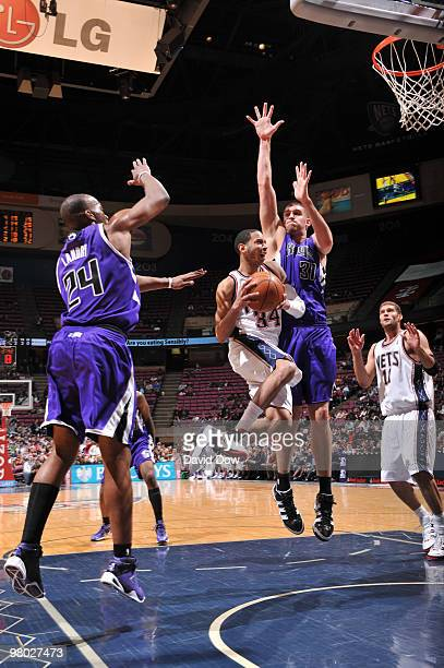 Devin Harris of the New Jersey Nets shoots against Carl Landry and Spencer Hawes of the Sacramento Kings during the game on March 24 2010 at the Izod...