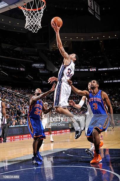 Devin Harris of the New Jersey Nets shoots over Shawne Williams and Toney Douglas of the New York Knicks on February 12 2011 at the Prudential Center...