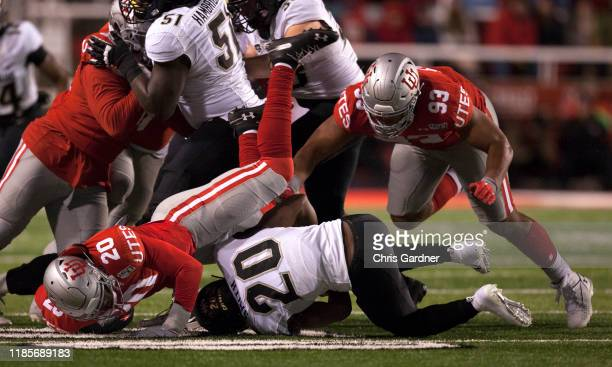 Devin Lloyd and Semisi Lauaki of the Utah Utes tackle Davion Taylor of the Colorado Buffaloes during the second half of their game at RiceEccles...