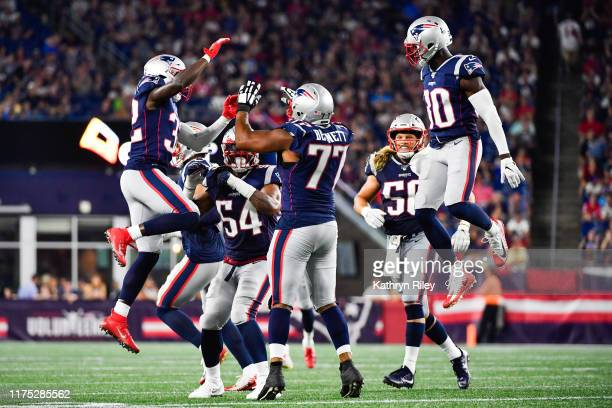 Devin McCourty celebrates with teammate Michael Bennett of the New England Patriots after completing a sack in the second quarter of a preseason game...