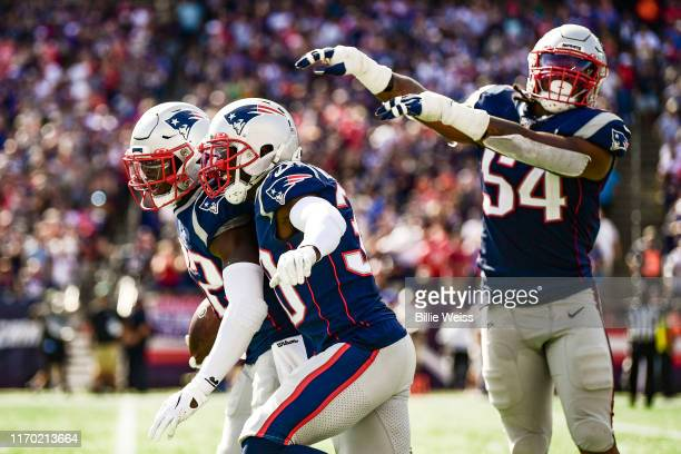Devin McCourty of the New England Patriots reacts with Jason McCourty after intercepting a pass during the third quarter of a game against the New...