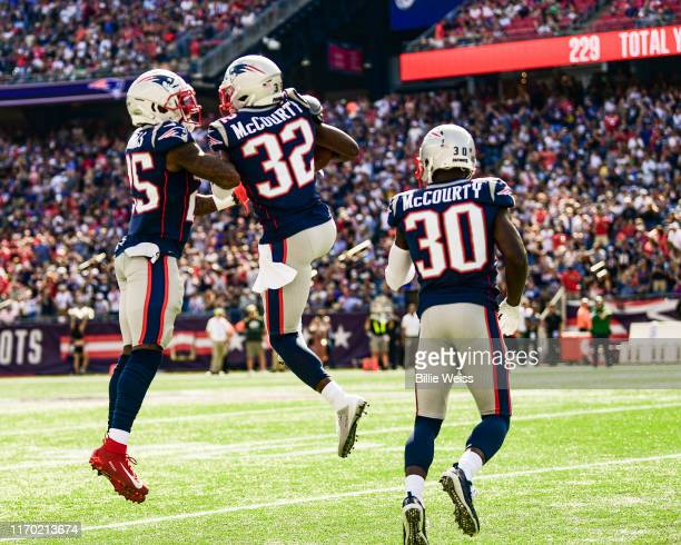 Devin McCourty of the New England Patriots reacts with Terrence Brooks and Jason McCourty after intercepting a pass during the third quarter of a...