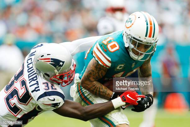 Devin McCourty of the New England Patriots tackles Kenny Stills of the Miami Dolphins during the second half at Hard Rock Stadium on December 9 2018...