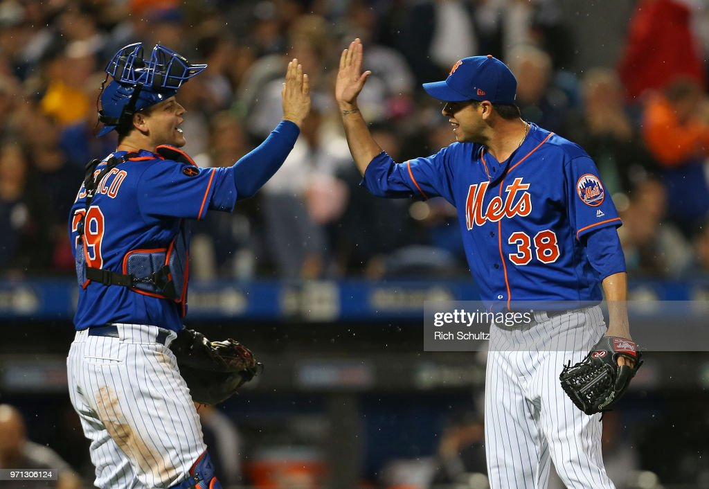 Devin Mesoraco #29 and Anthony Swarzak #38 of the New York Mets celebrate their 2-0 win over the New York Yankees during a game at Citi Field on June 10, 2018 in the Flushing neighborhood of the Queens borough of New York City.