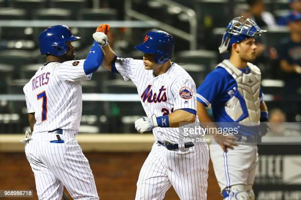 Devin Mesoraco of the New York Mets is greeted by Jose Reyes after hitting a 2run home run in the eighth inning against the Toronto Blue Jays at Citi...