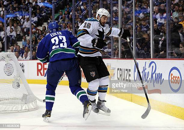 Devin Setoguchi of the San Jose Sharks bounces off a check by Alexander Edler of the Vancouver Canucks in the first period in Game Five of the...