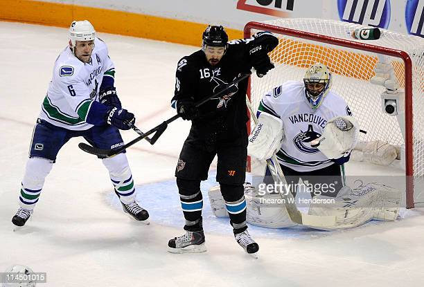 Devin Setoguchi of the San Jose Sharks deflects the puck on net as Sami Salo and goaltender Roberto Luongo of the Vancouver Canucks defend the play...