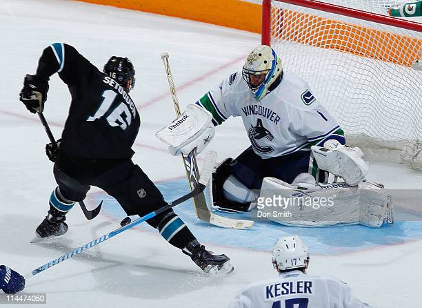 Devin Setoguchi of the San Jose Sharks handles the puck in front of the net against Roberto Luongo of the Vancouver Canucks in Game Three of the...
