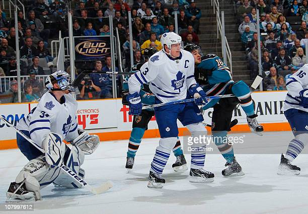 Devin Setoguchi of the San Jose Sharks is upended against Dion Phaneuf and James Reimer of the Toronto Maple Leafs during an NHL game on January 11,...