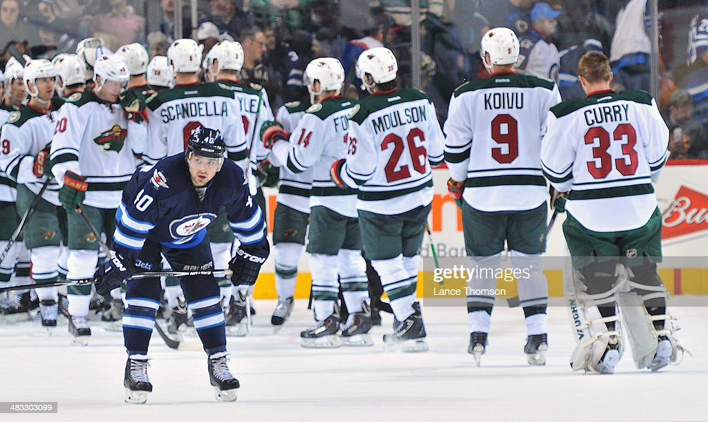 Devin Setoguchi #40 of the Winnipeg Jets skates away dejected as members of the Minnesota Wild celebrate a 1-0 victory at the MTS Centre on April 7, 2014 in Winnipeg, Manitoba, Canada.