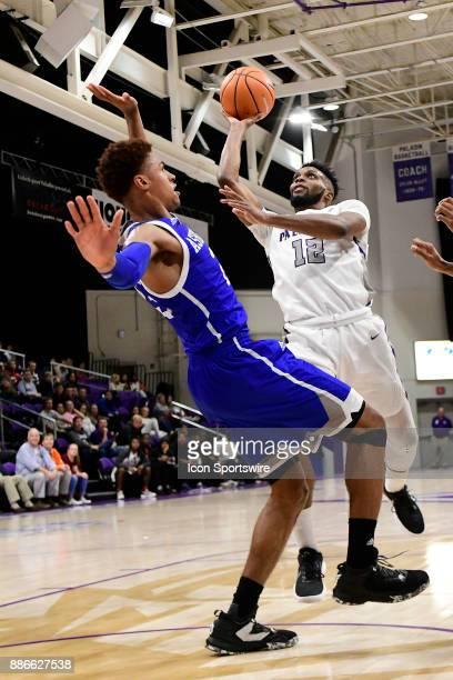 Devin Sibley guard Furman University Paladins takes a shot over MaCio Teague guard UNC Asheville Bulldogs Tuesday December 5 at Timmons Arena in...
