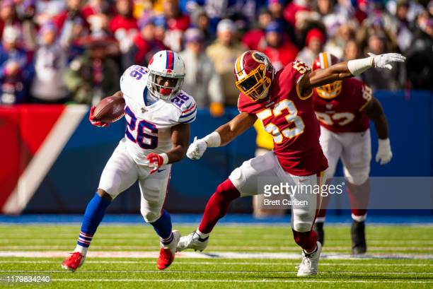 Devin Singletary of the Buffalo Bills runs with the ball for a first down as he is pursued by Jon Bostic of the Washington Redskins during the first...