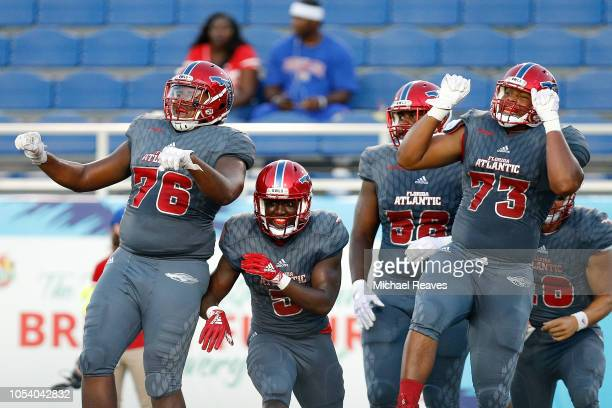 Devin Singletary of the Florida Atlantic Owls celebrates with teammates after a touchdown against the Louisiana Tech Bulldogs during the first half...