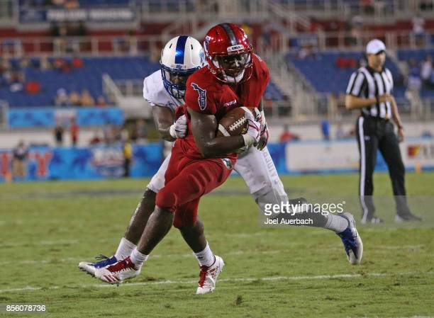 Devin Singletary of the Florida Atlantic Owls is stopped short of the goal line by DJ Sanders of the Middle Tennessee Blue Raiders on September 30...