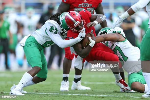 Devin Singletary of the Florida Atlantic Owls is tackled by Ashton Preston and Brandon Garner of the North Texas Mean Green on October 21 2017 at FAU...