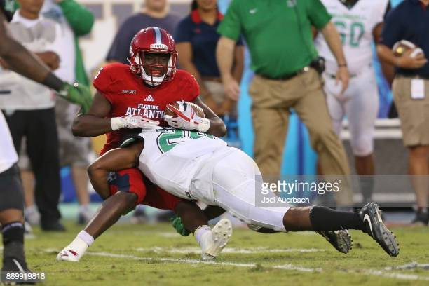 Devin Singletary of the Florida Atlantic Owls is tackled by Malik Gant of the Marshall Thundering Herd as he runs with the ball during second quarter...