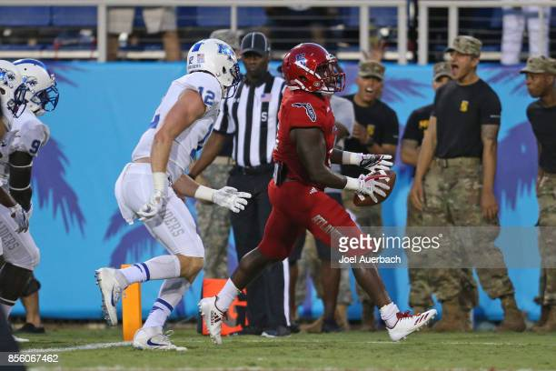 Devin Singletary of the Florida Atlantic Owls runs past Reed Blankenship of the Middle Tennessee Blue Raiders for a touchdown during first quarter...