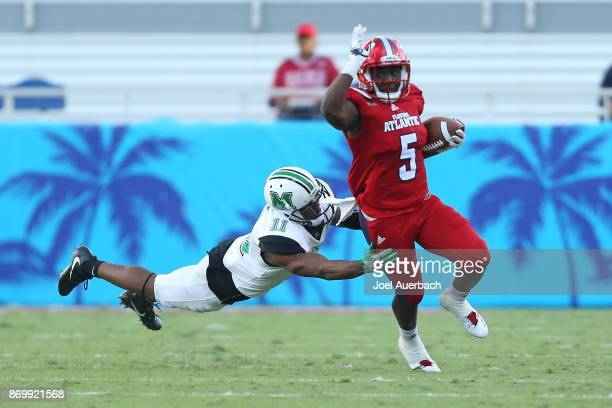 Devin Singletary of the Florida Atlantic Owls runs past the attempted tackle by Rodney Allen of the Marshall Thundering Herd at FAU Stadium on...